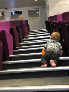 baby crawls up lecture theatre stairs