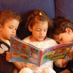 3 children reading magazine